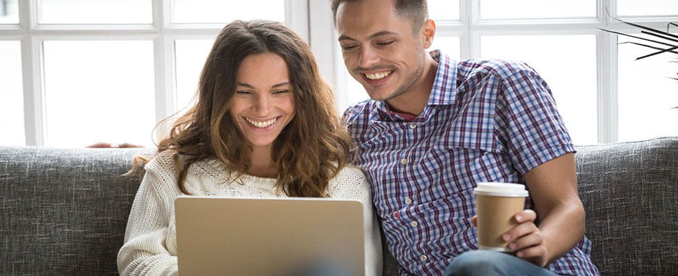 Smiling young couple enjoying morning coffee with computer, sitting on sofa at home together; happy man and woman laughing looking on laptop screen having fun while programming